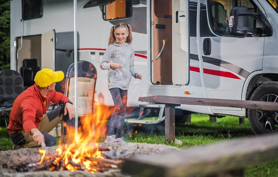 Father and daughter camping by the campfire