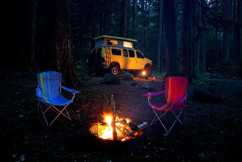 Chairs sitting by the campfire outside camper van