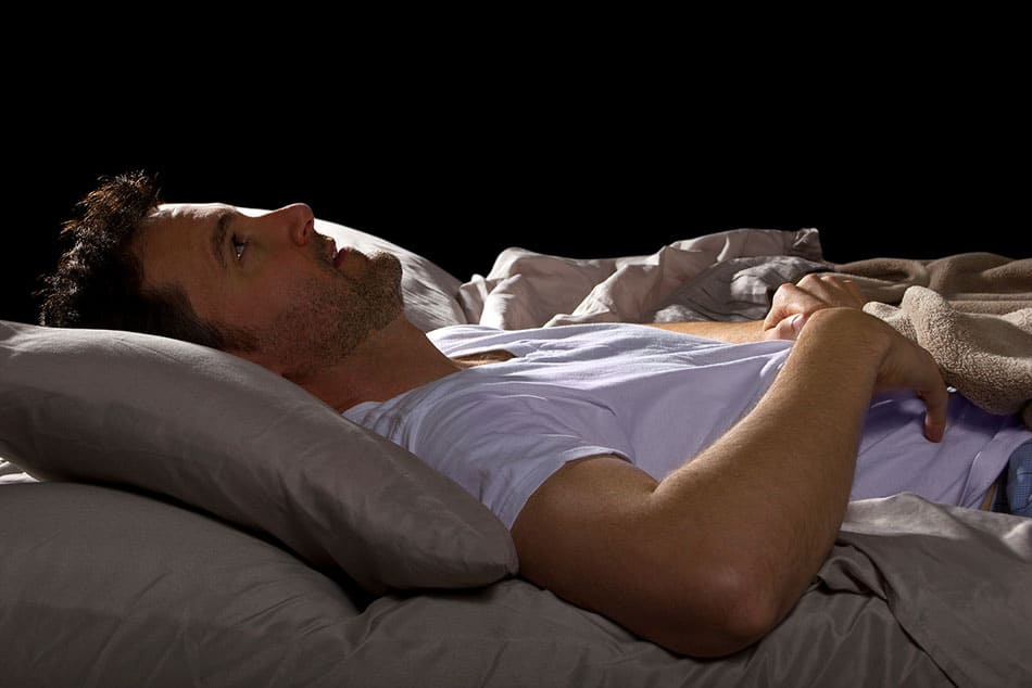 Man laying in bed having trouble sleeping