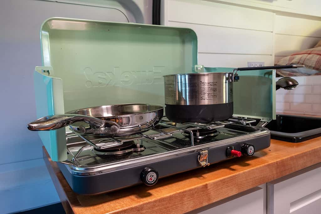 Camp stove with saucepan and skillet on top