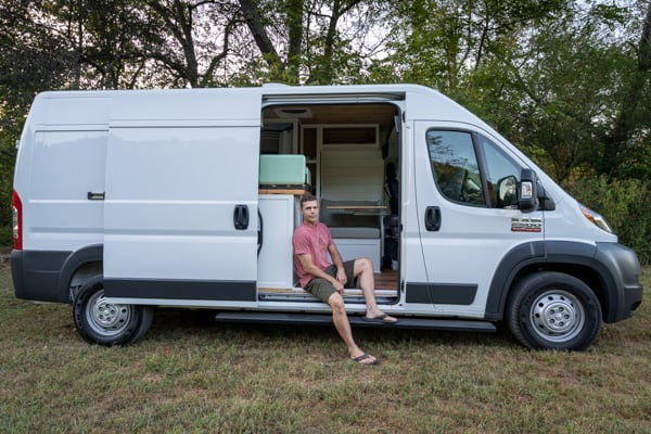 Dan Collins sitting in door of camper van.