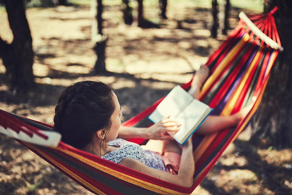 Woman at campground reading book in hammock