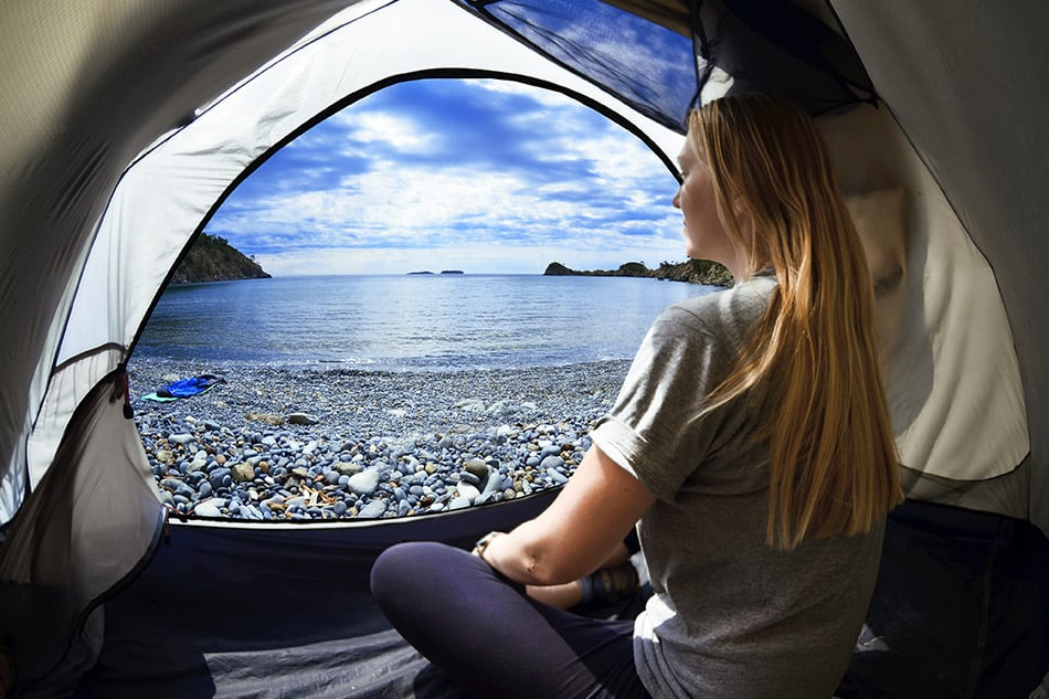 Woman looking out of tent on beach