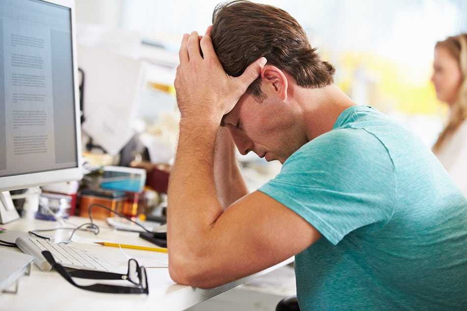 Man at office desk with head in hands